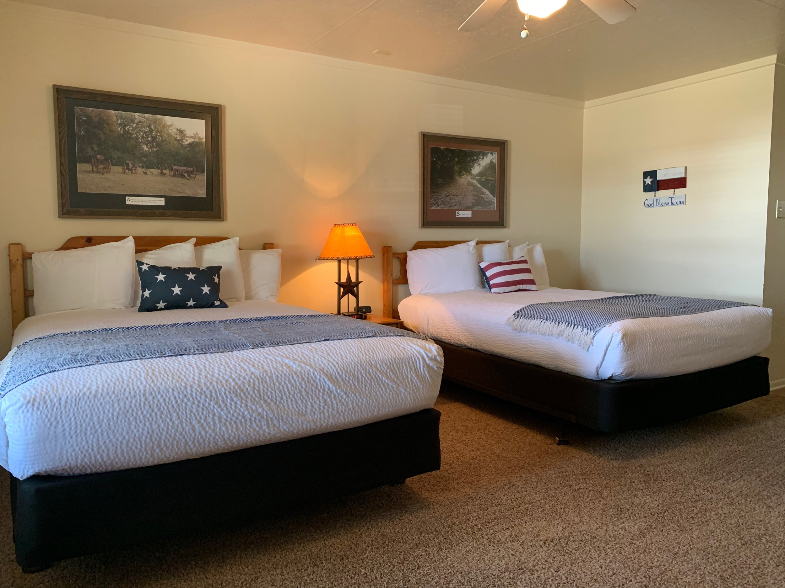 Texas Suites - Texas provides 5 individual spacious suites with private entrances to the outside. Each room has 2 queen beds, a private bath, and a kitchenette. The rooms at Texas are centrally located near huge oak trees and overlook the old Chisholm Ostrich Farm and rec courts. [Accommodates 5-20 people]