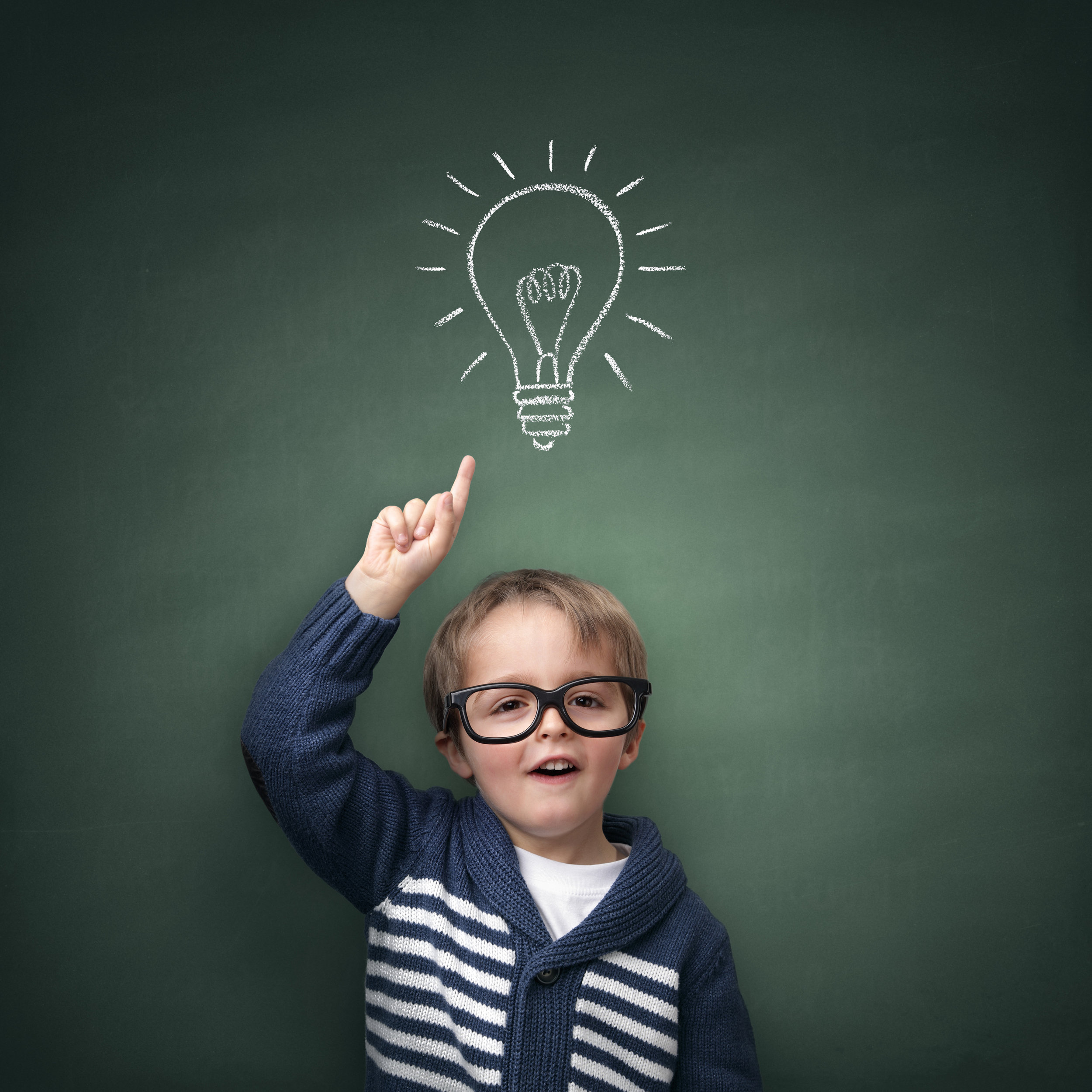 Schoolboy standing in front of a blackboard with a bright idea light bulb above his head concept for.jpg