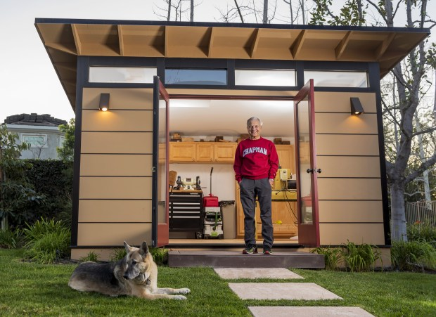 Jim Doti, former Chapman University president, and his dog Angel, is shown at the 12-by-14-foot studio shed he uses as his backyard woodshop in Villa Park on Thursday, Feb. 15, 2018. (Photo by Leonard Ortiz, Orange County Register/SCNG)