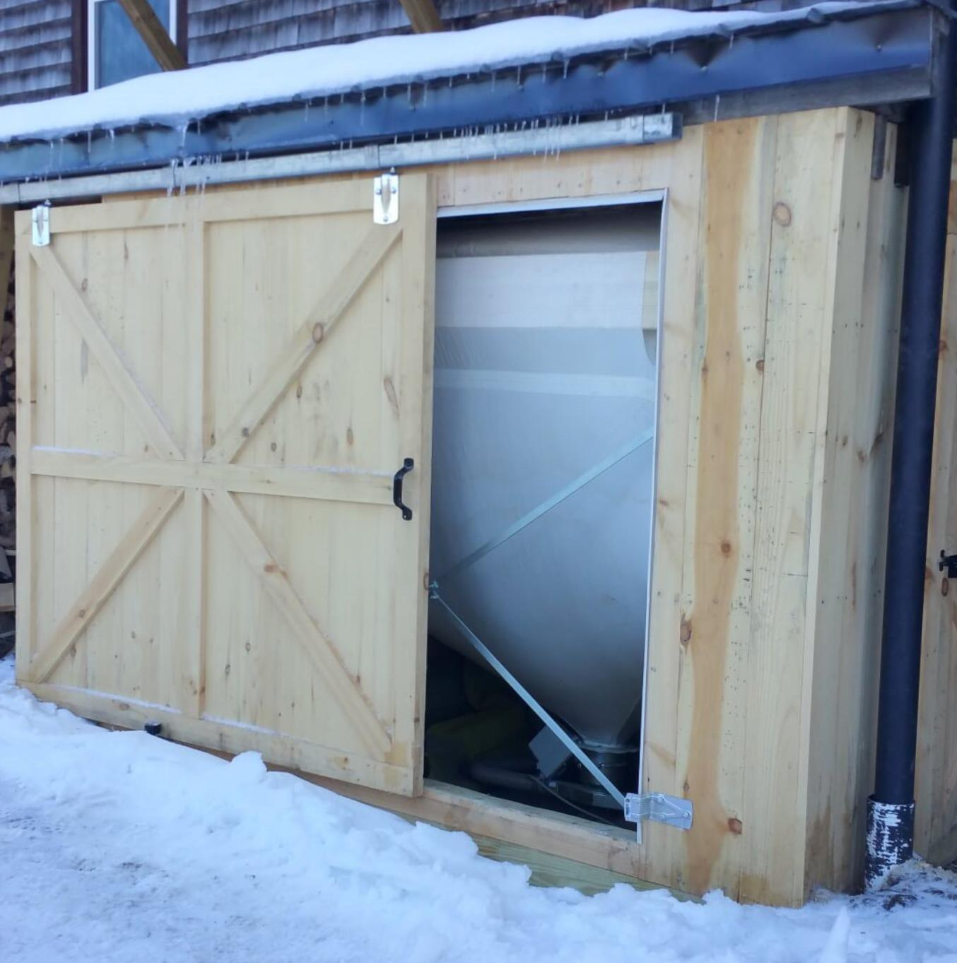Wood pellets are delivered in bulk by truck to this outdoor pellet-storage bin. Pellets are automatically fed, on-demand, to the boiler that heats this residence. - Energize Vermont