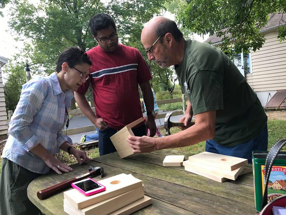 Board of Trustee member, Chris Berry, teaching volunteers how to build bird houses.