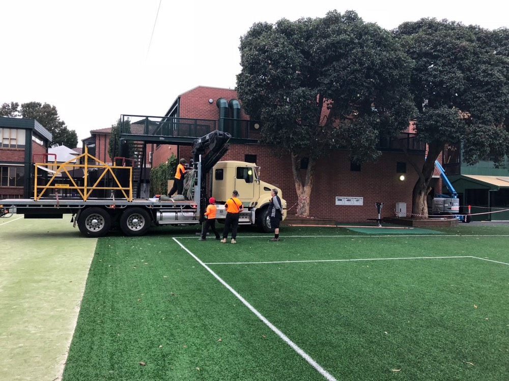 AC unit & crane vehicle setting up outside in a school ground