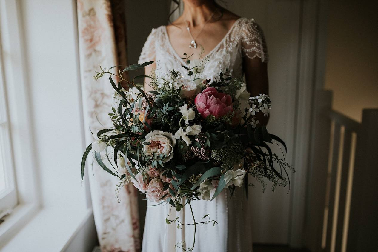 Bride holding pastel, coral bridal bouquet by window