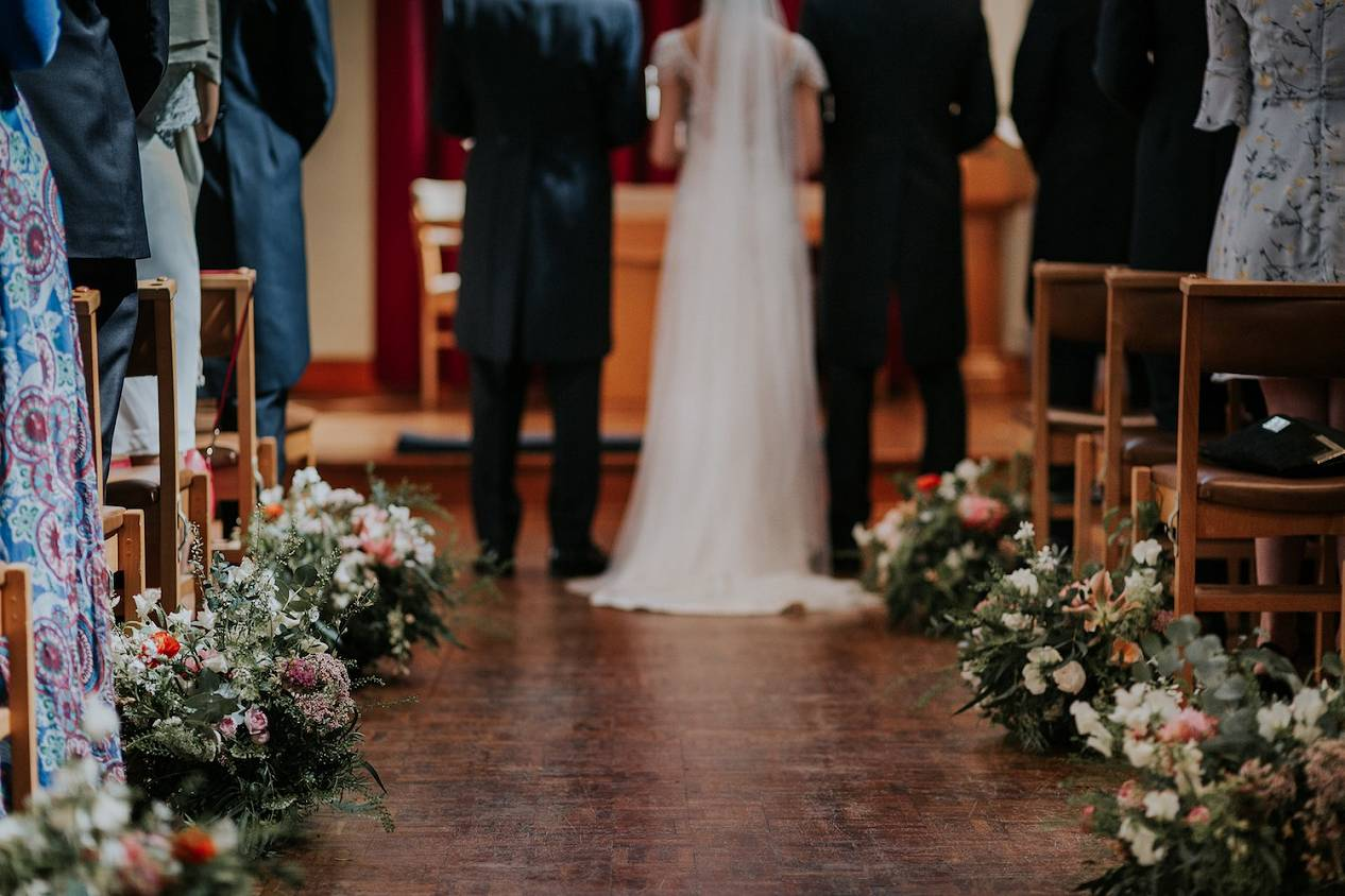 Church wedding aisle with meadow flowers and bride and groom