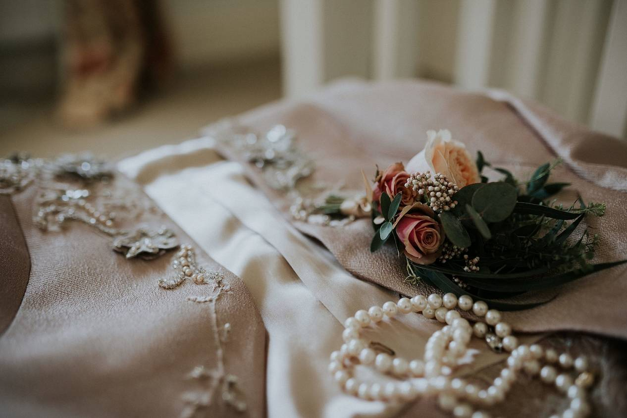 Corsage with roses and creamy white wedding outfit