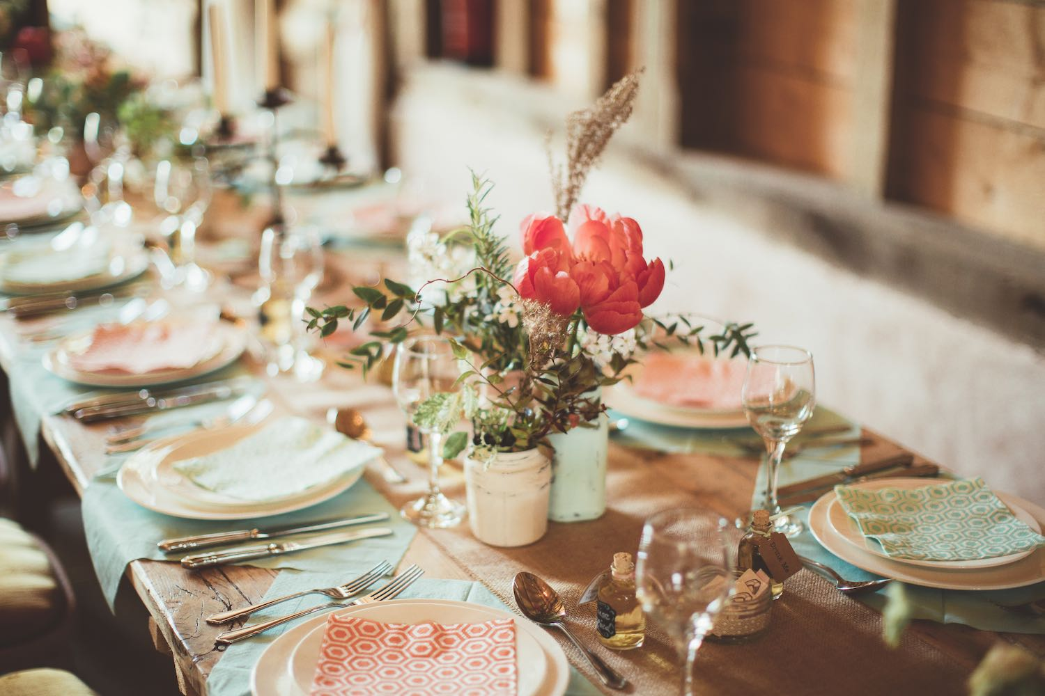 Pastel wedding table setting with jam jar flowers