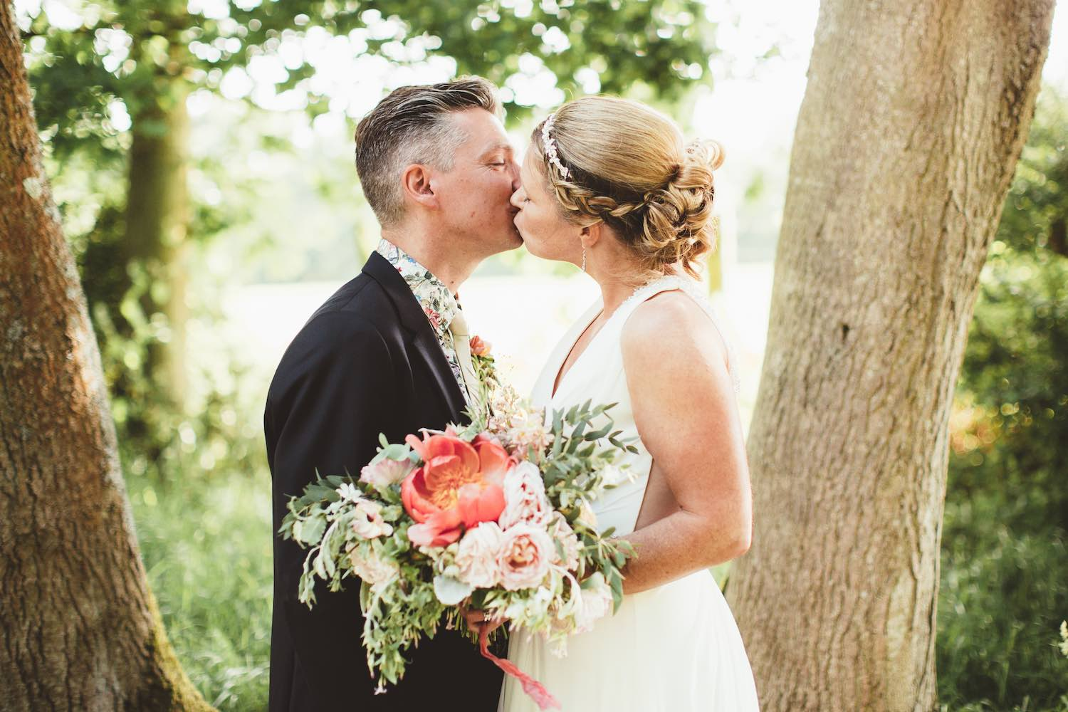 Bride and groom kissing under the tree holding bouquet
