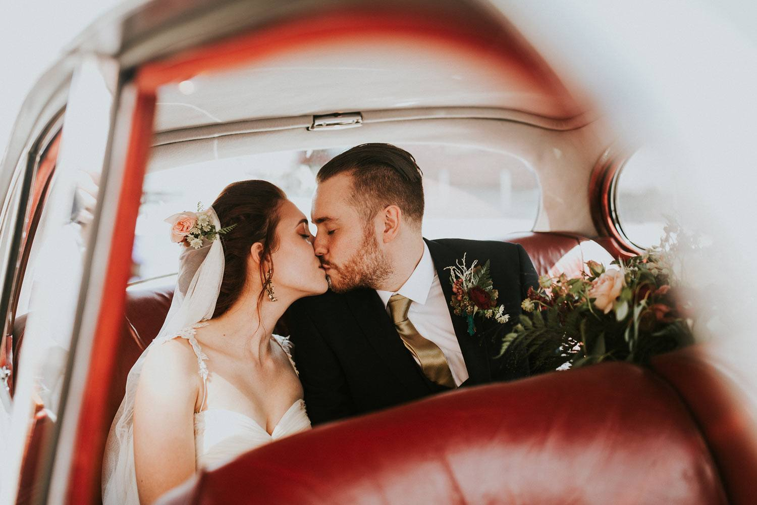 Couple kissing in wedding car with flowers