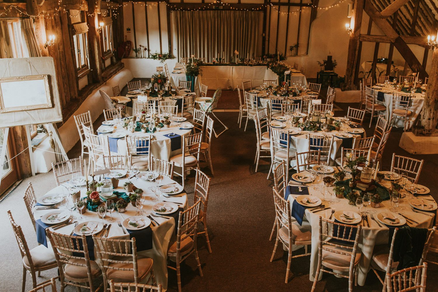 Round wedding tables in barn with flowers