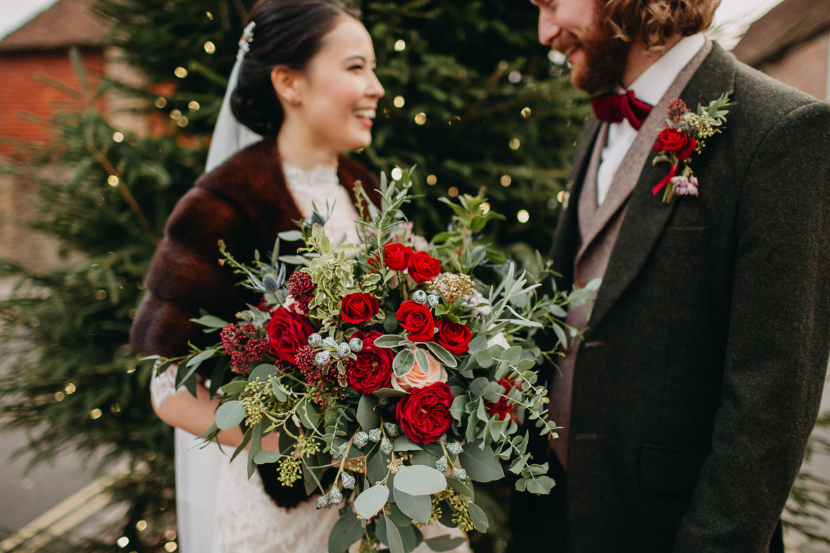 Winter bride and groom outside church with red rose bouquet