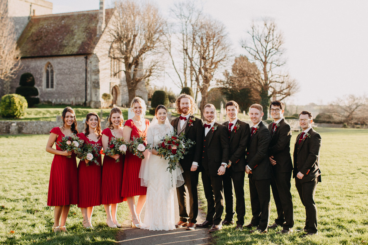 Winter bride, bridesmaids and groom with groomsmen outside church