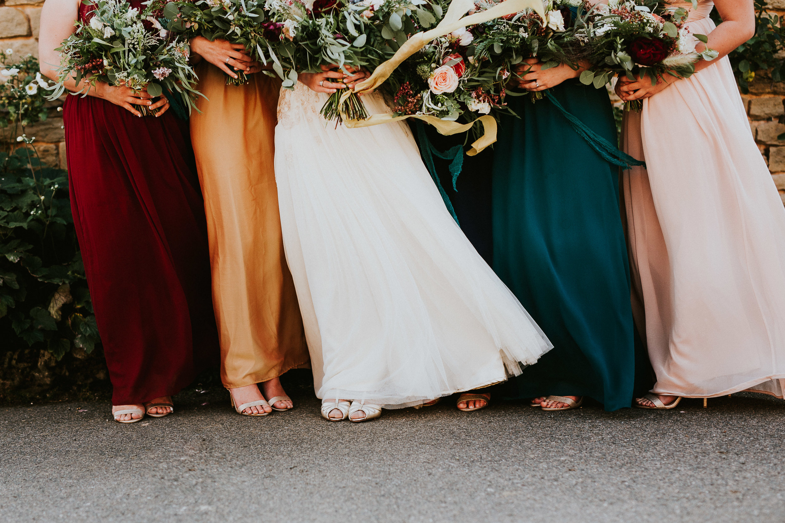 Colourful bridesmaids dresses with rustic woodland bouquets