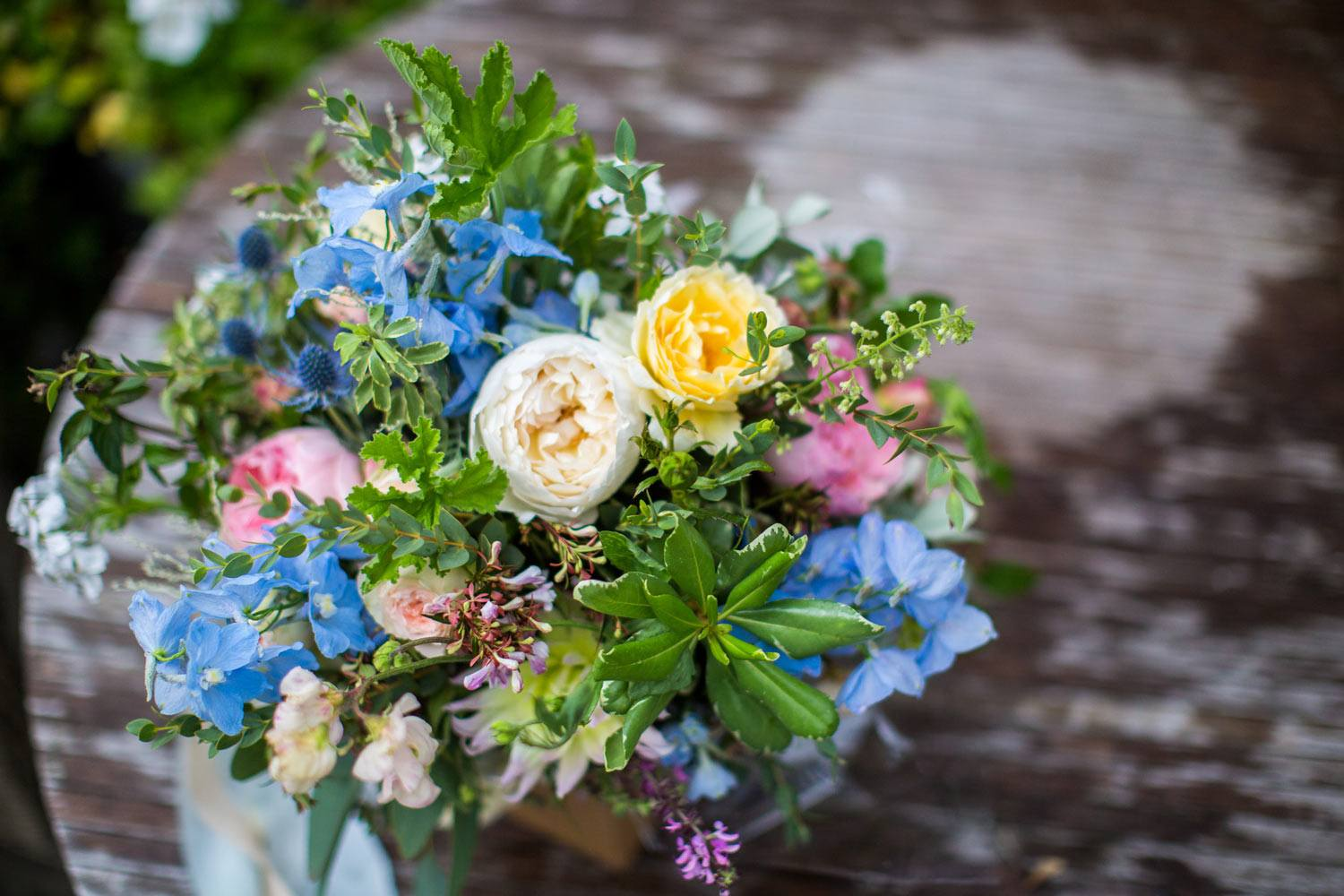 Blue, pale yellow and pale pink bridal bouquet on table