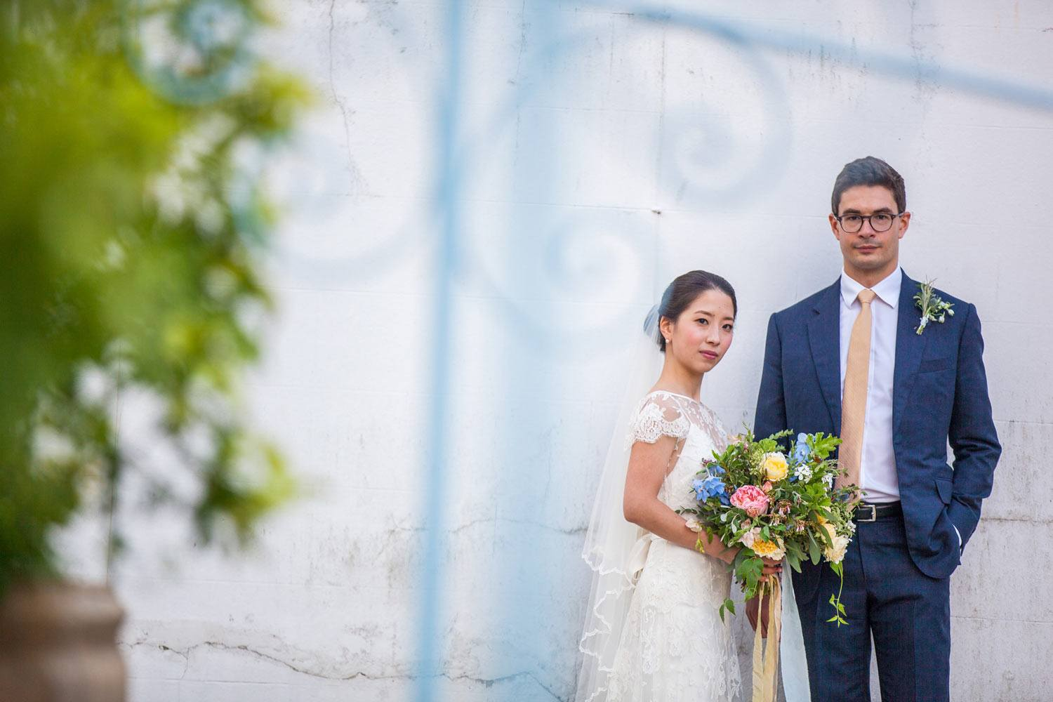 Bride and groom in front of white building with flowers