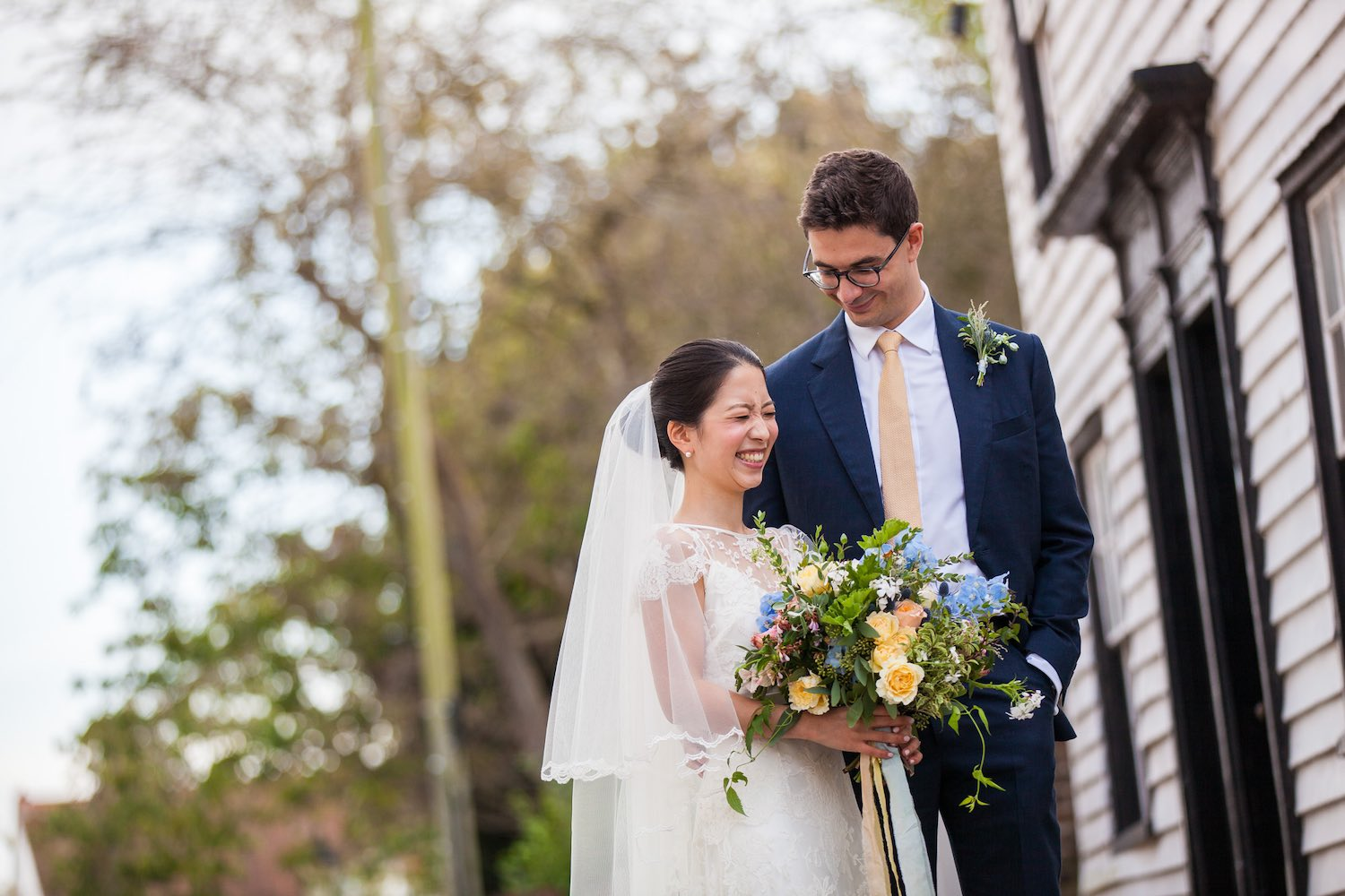 Bride and groom with garden bouquet outside white cladded building
