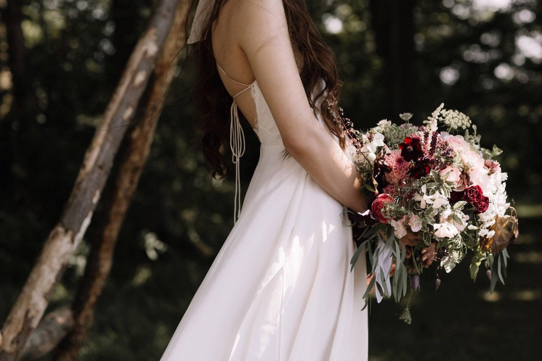 Bride holding dark velvety bridal bouquet