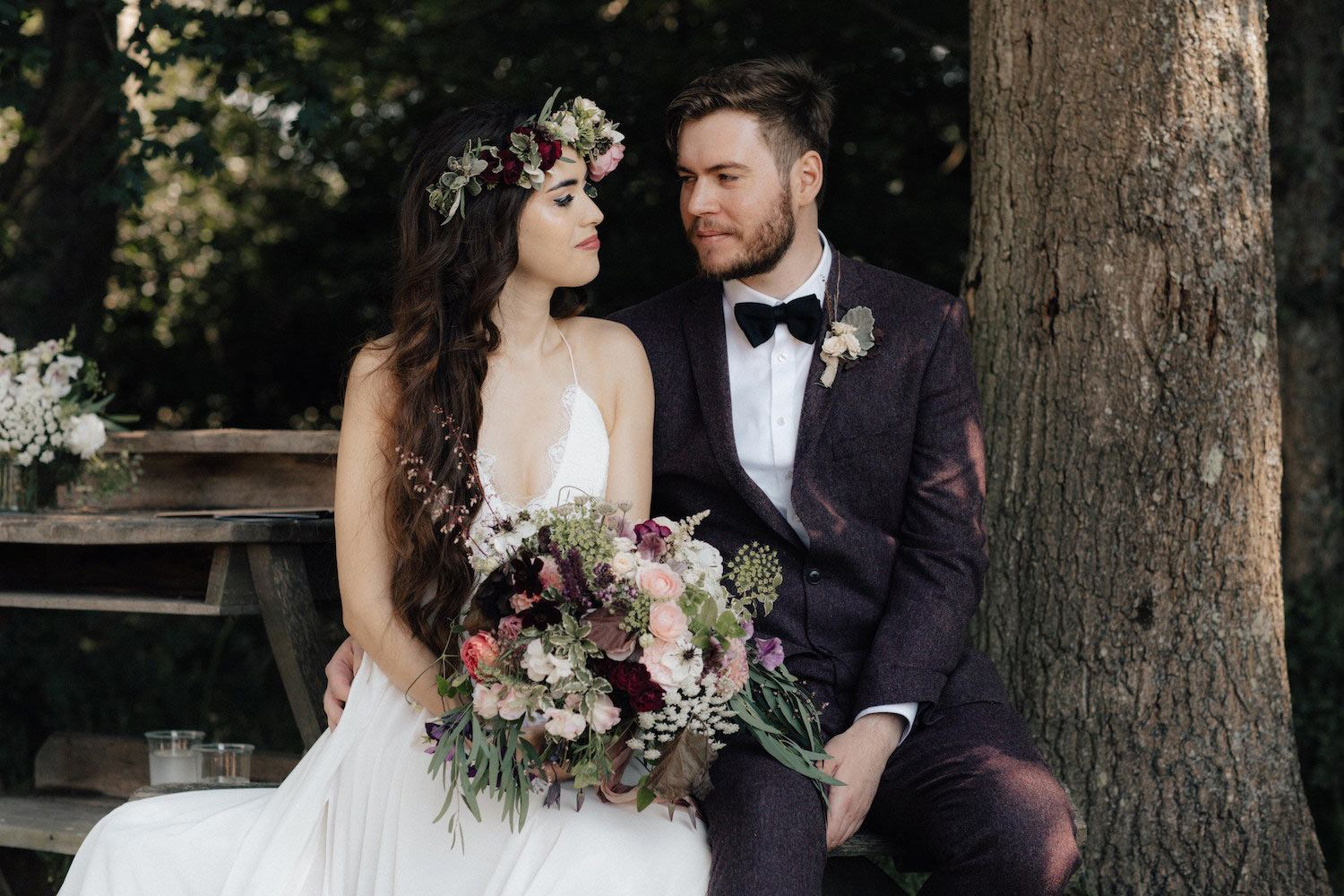 Bohemian bride and groom sitting in woodland ceremony