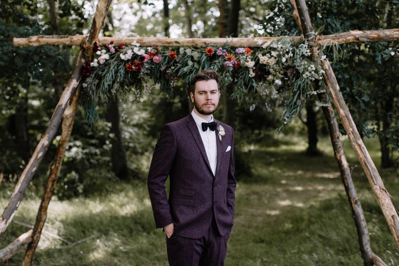 Groom standing under woodland wedding arch