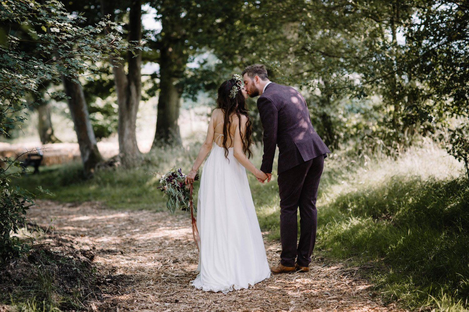 Bohemian bride and groom kissing in woodland path