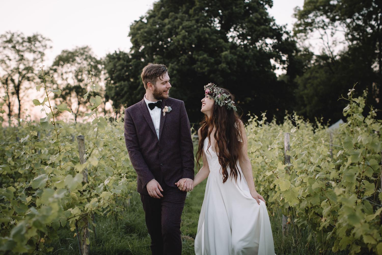 Bohemian wedding couple walking through vineyard