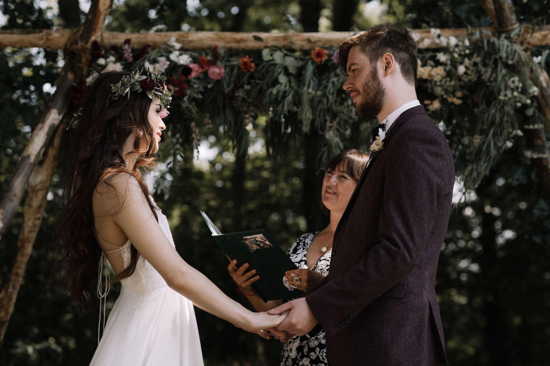 Woodland wedding ceremony couple holding hands