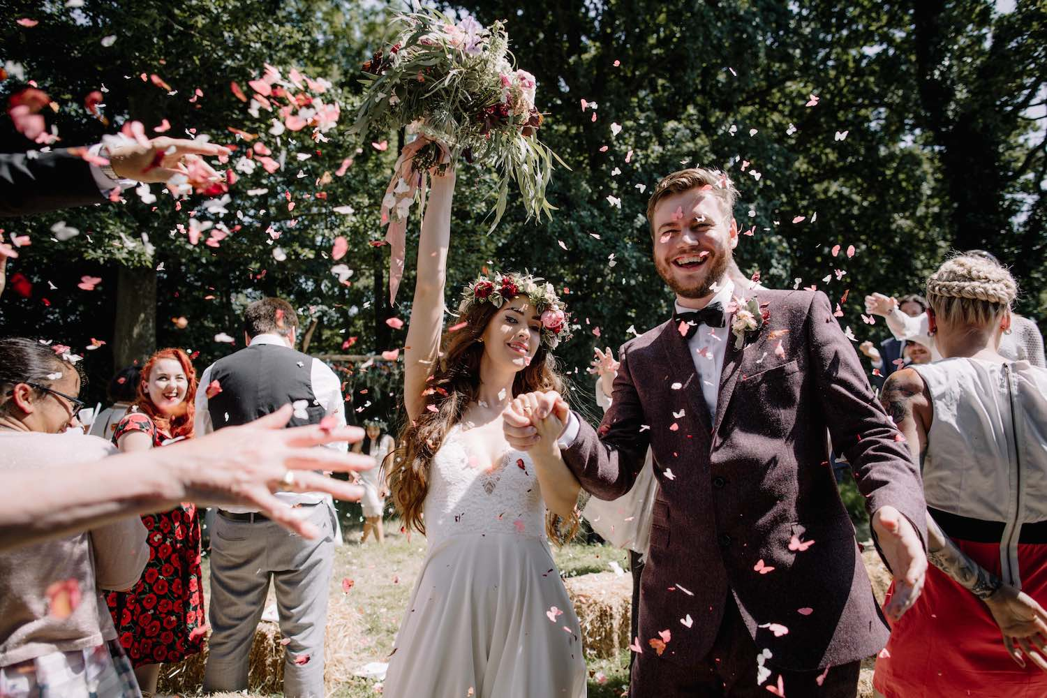 Couple cheering with confetti after woodland ceremony