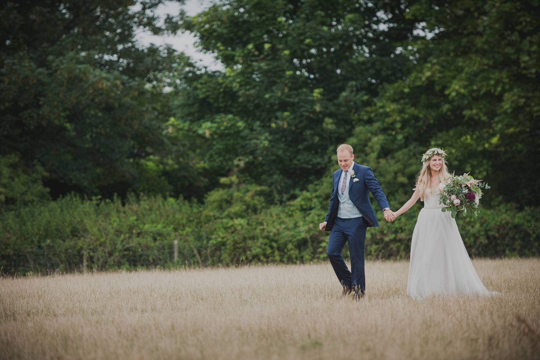 Bride and groom walking in summer meadow