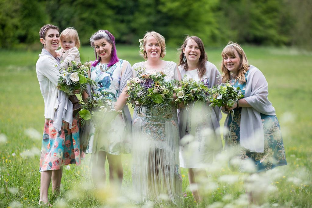 Bride and bridesmaids in spring meadow with wild bouquets