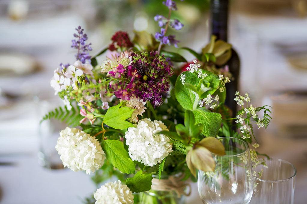 spring wild flowers in jar on wedding table