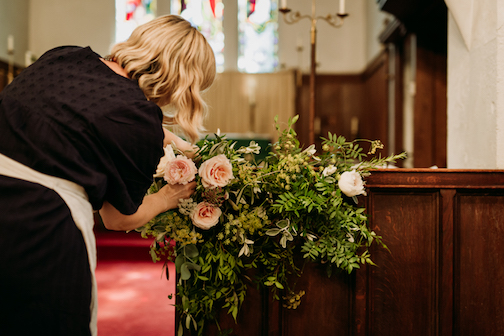 Bea arranging roses on church altar