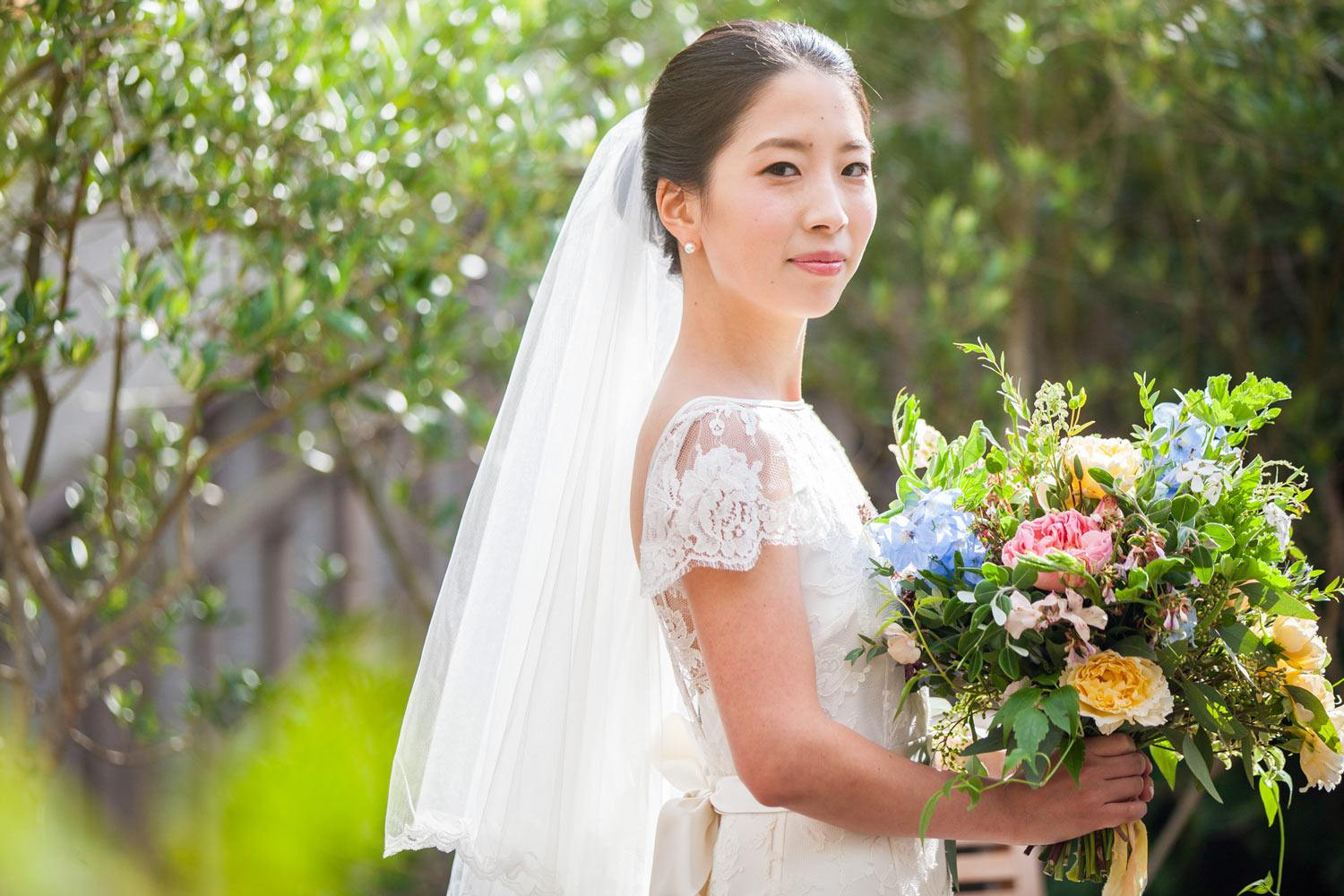 Japanese bride holding garden bouquet in garden