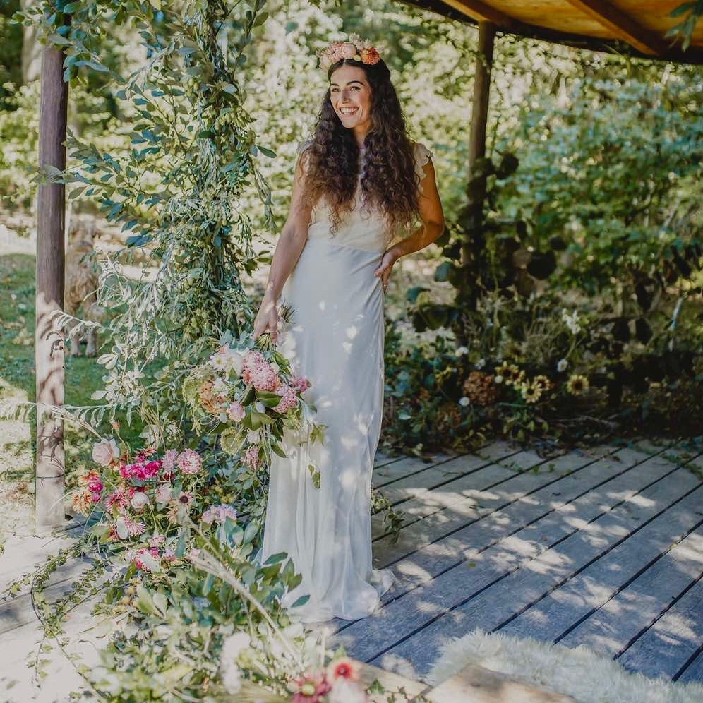 Bride in natural flower background holding bouquet