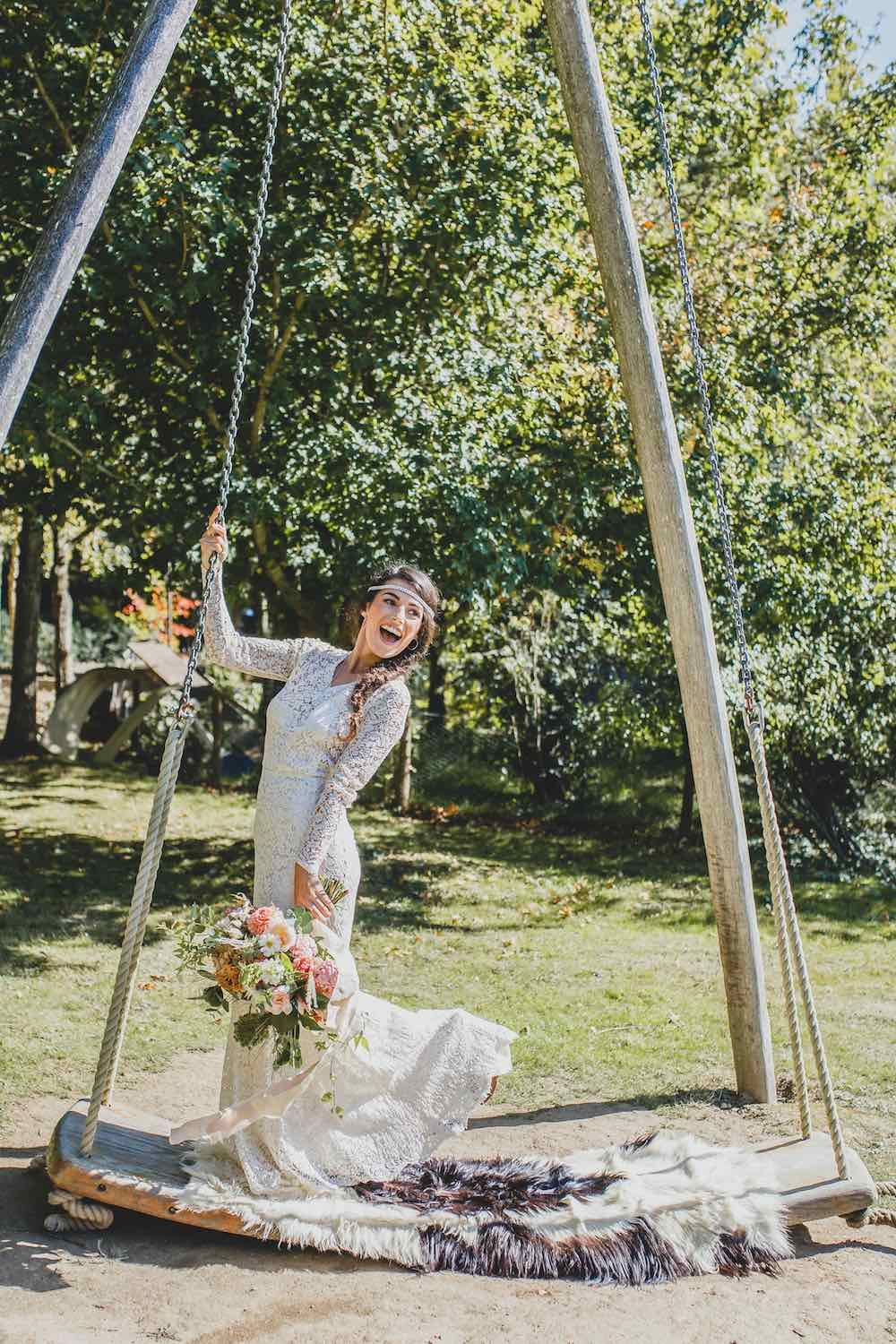 Bride on giant woodland swing with flowers