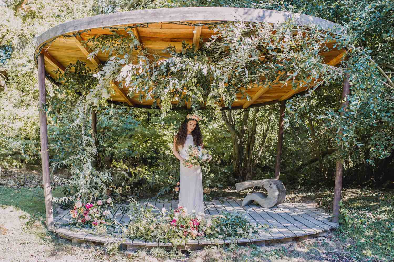 Bride in woodland ceremony stage with flowers