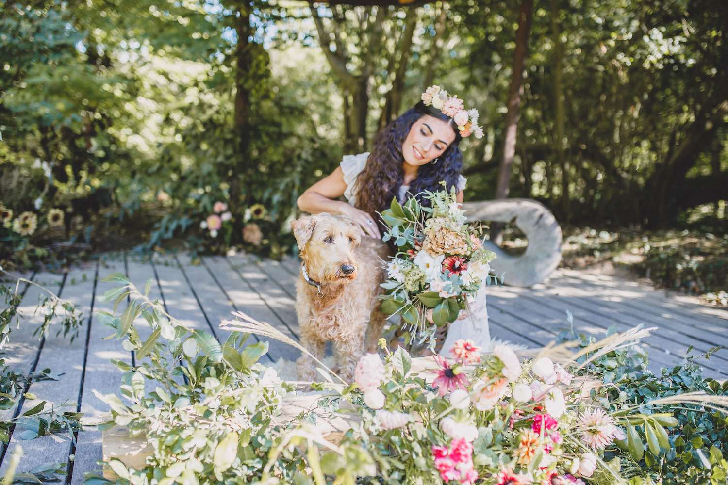 Woodland bride with flowers and dog on ceremony stage