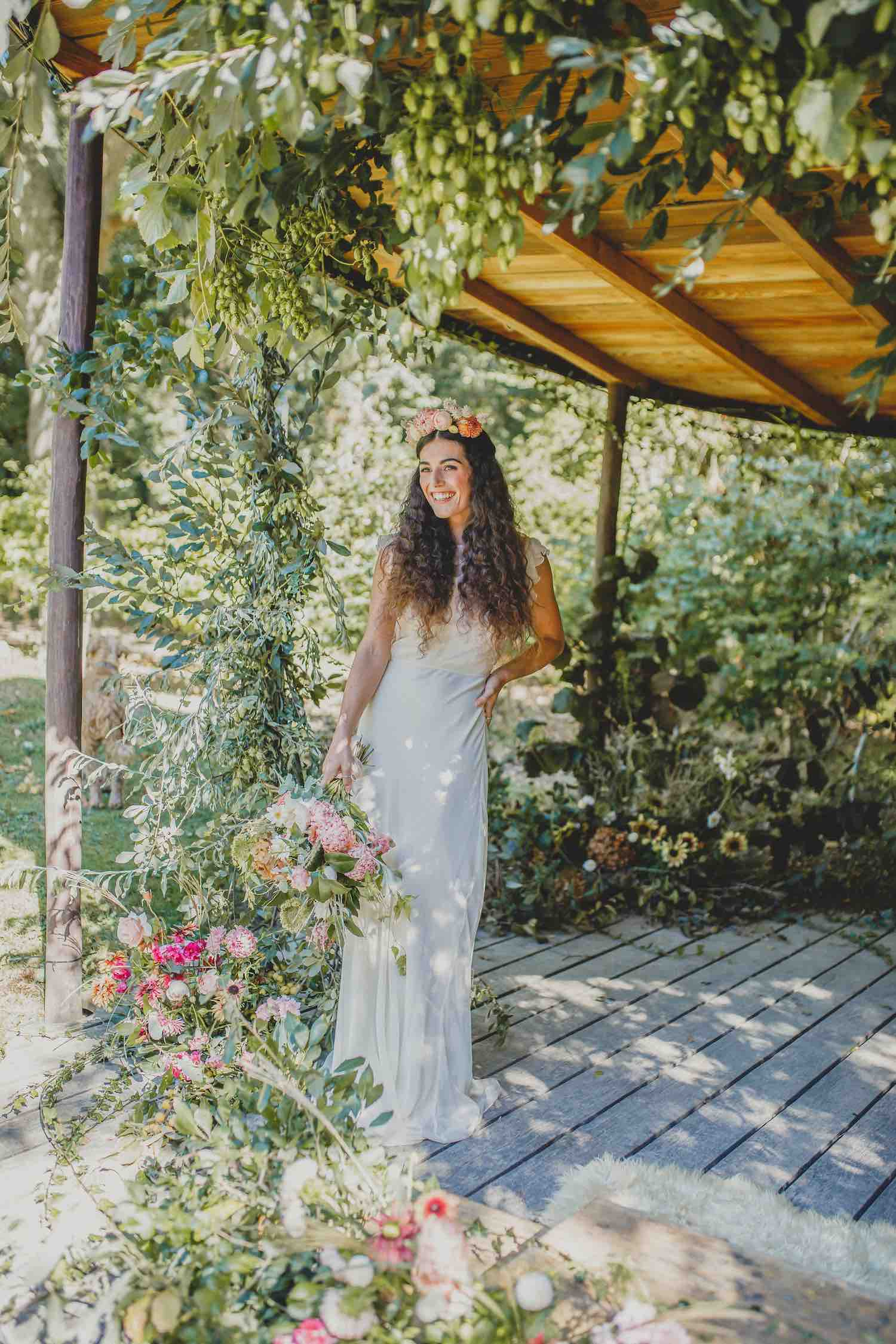 Woodland bride surrounded by woodland ceremony arch flowers