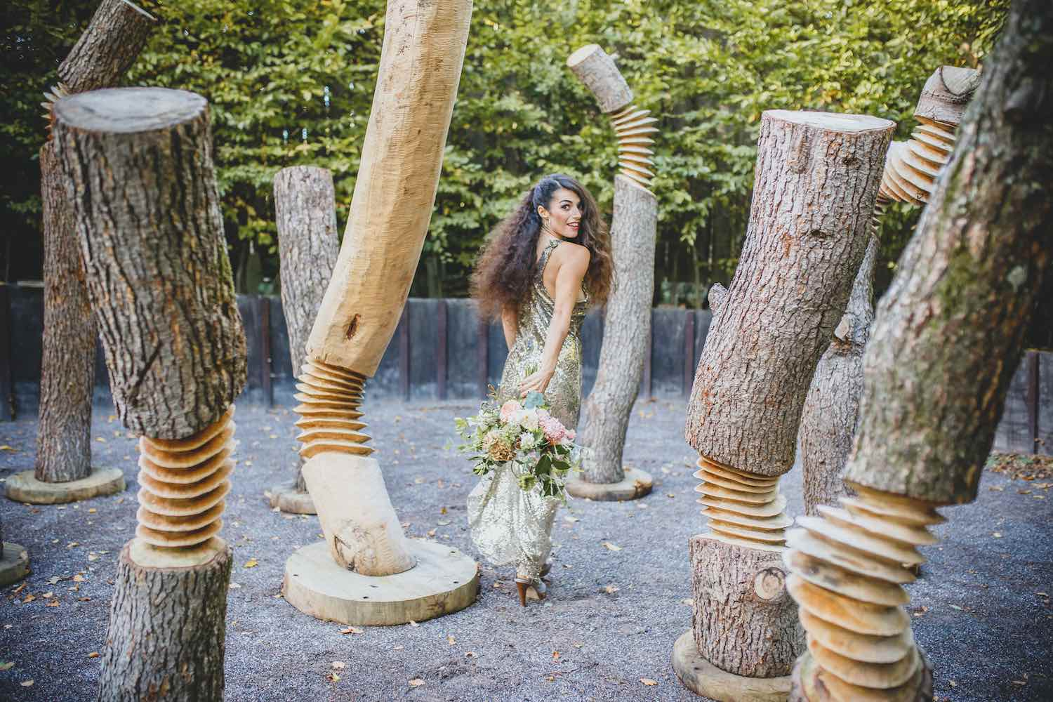 Bride with bouquet in woodland sculpture park