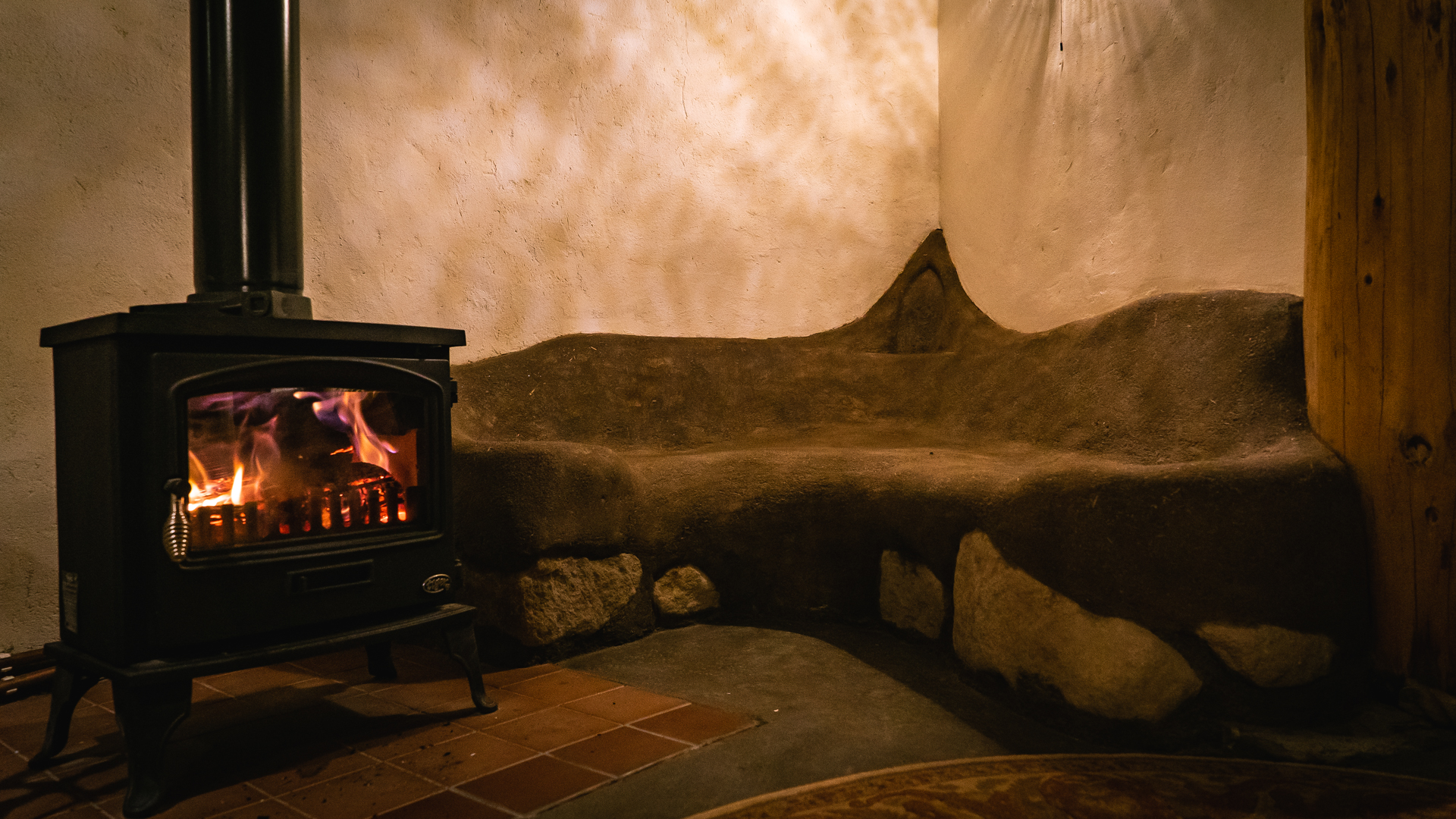 Wood-burning stove & hand-built, cob, snuggle-seat