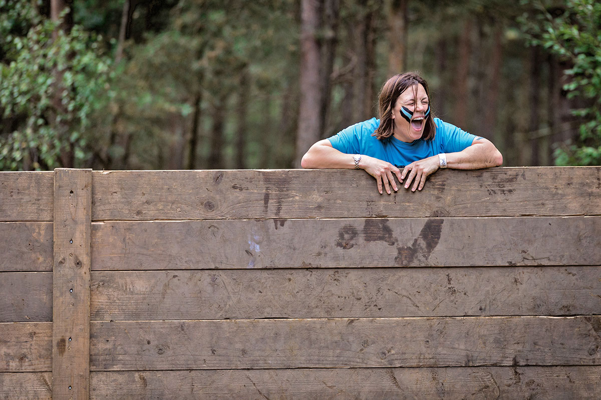 Woman laughs at top of the wall