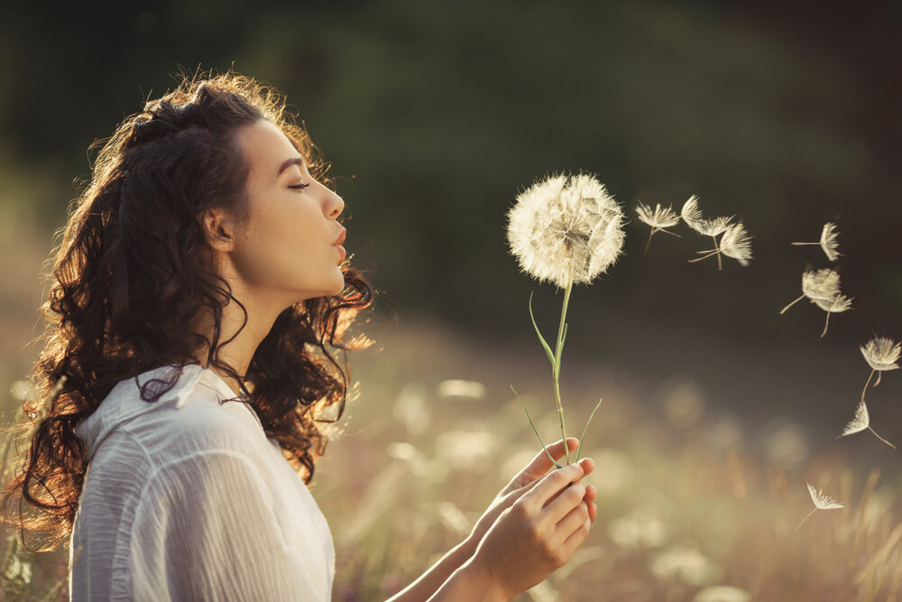 Beautiful Woman Blowing The dandelion