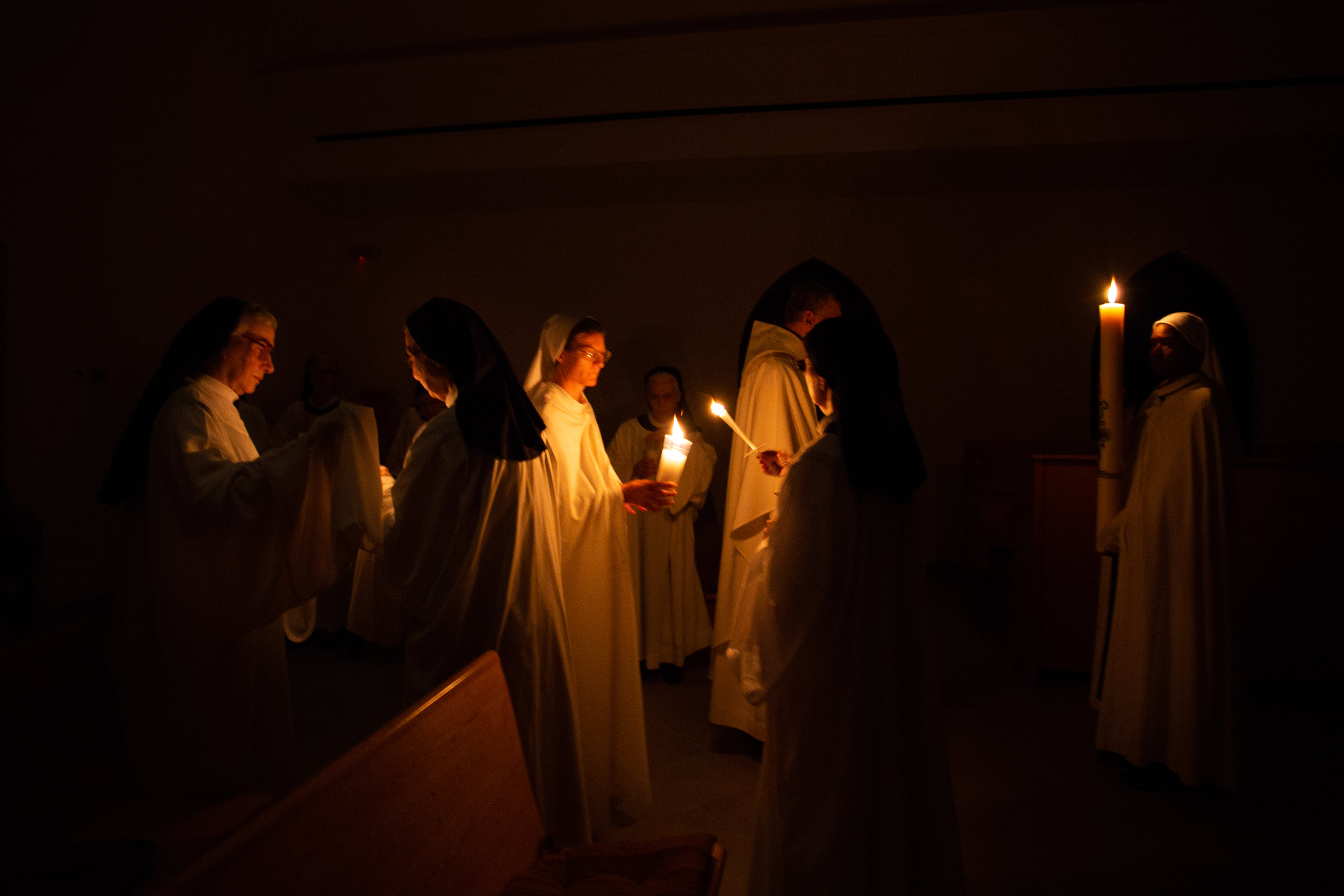 The sisters and guests stand in silence as they light candles Saturday evening April 20, 2019 in Crozet, Virginia. This ends their procession into the church for Easter mass.