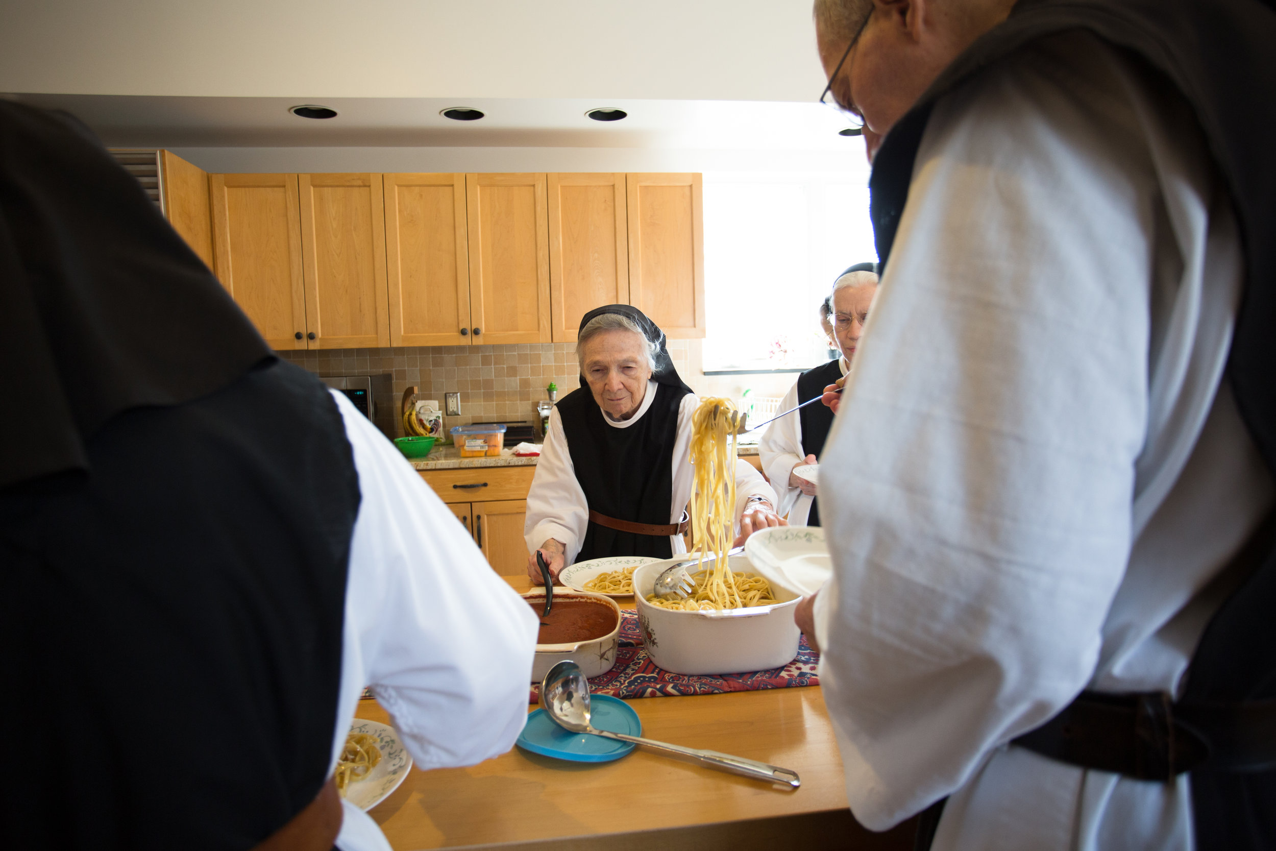 Sister Claire dishes out spaghetti sauce before supper. The sisters eat family style because it is another way to emphasize community and sharing of blessings. Their Gouda cheese is also served on the table.