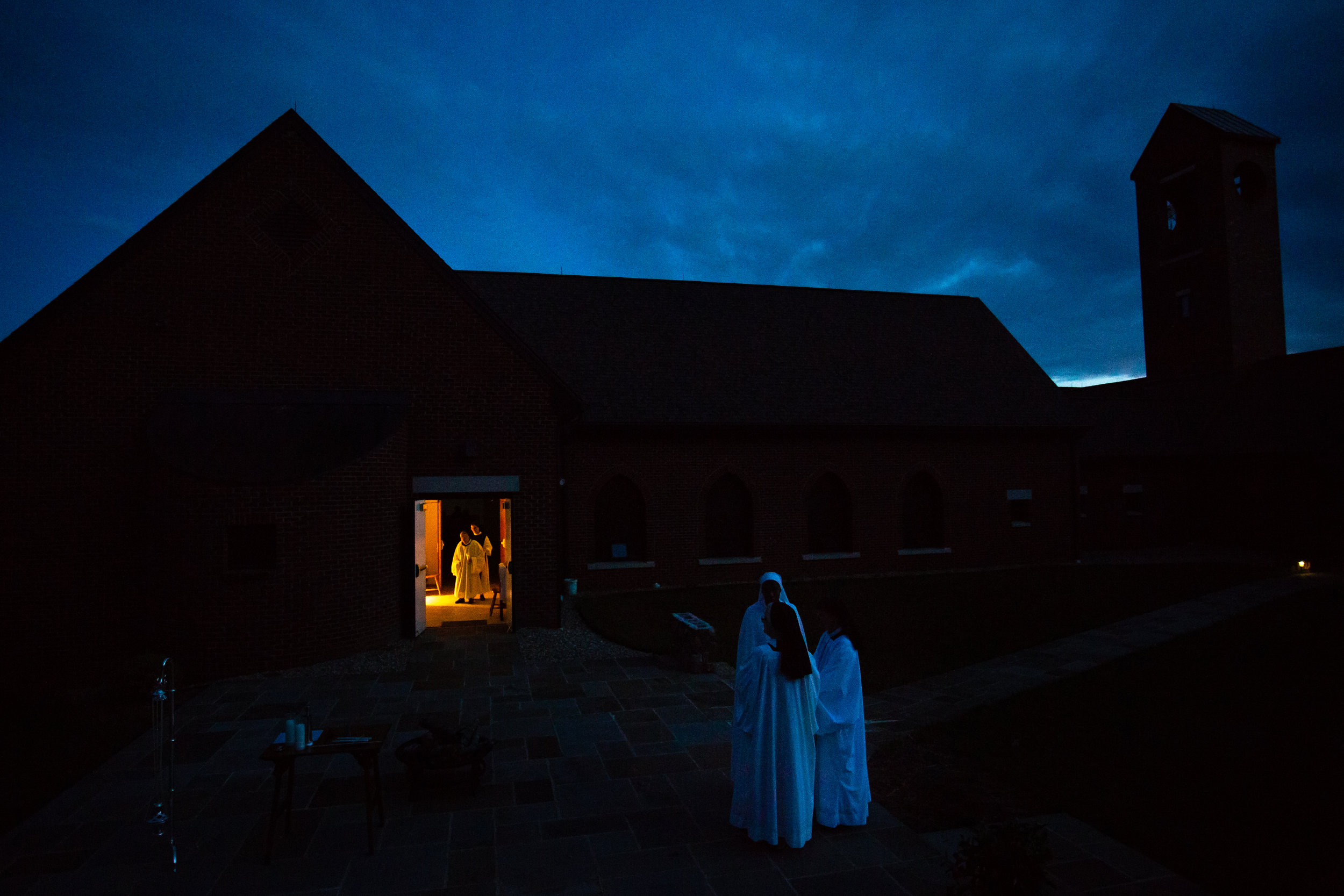 The sisters prepare the patio with candles and a fire for Easter service Saturday evening April 20, 2019 in Crozet, Virginia. Once the guests arrive this begins their procession into the church for Easter mass.