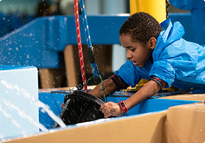 A young boy in a blue raincoat scoops water into a bucket in the WaterWays exhibit