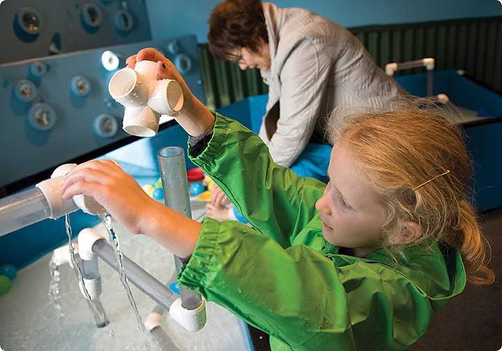A young girl in a green raincoat pulls plastic levers and experiments with water flow in the WaterWays exhibit