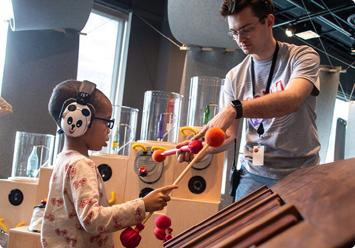 A Chicago Children's Museum staff member teaches a little boy to play a marimba with mallets