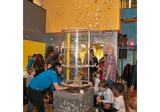 Copy of CCM staff help little ones play with a wind tunnel as it blows fake snow into the air