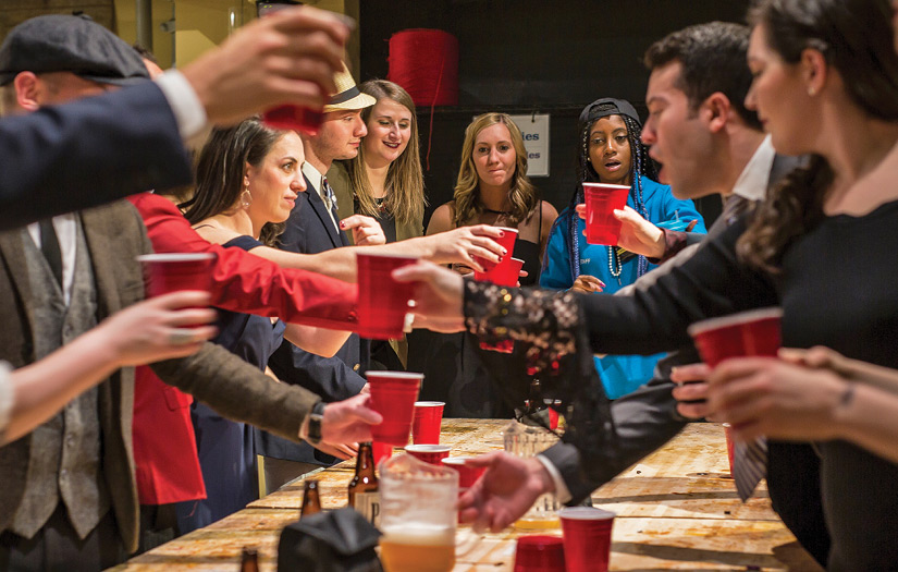 A group of formal-clad men and women toast beer glasses over a Tinkering Lab table