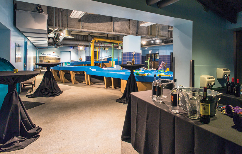 The WaterWays exhibit set up for an evening event featuring black tablecloth covered high boy tables and a bar
