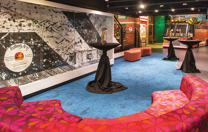 A view of the museum's 2nd floor set up for a cocktail party, featuring high boy tables scattered amongst the art and fire truck.